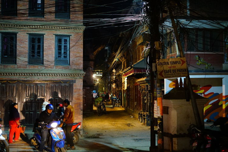 People on street amidst buildings in city at night