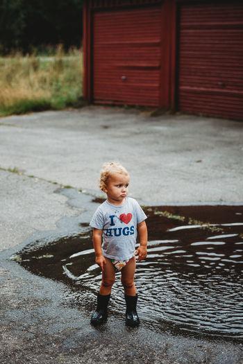 Full length of cute boy standing on footpath