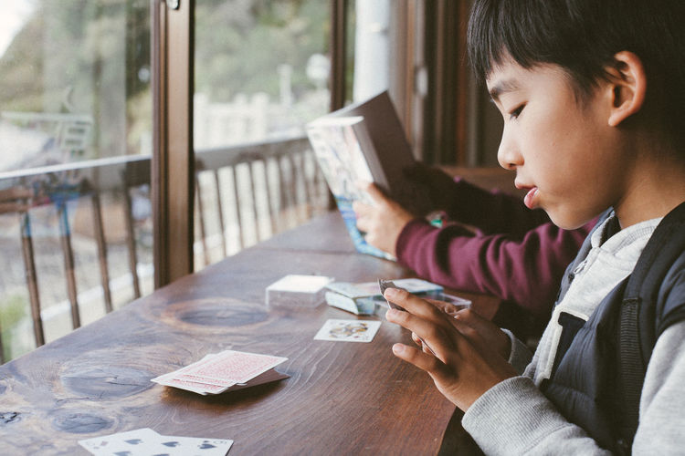 Close-up of boy using mobile phone on table