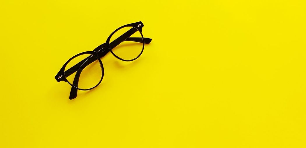 High angle view of eyeglasses against yellow background