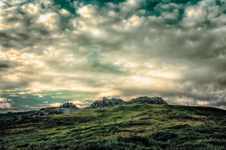 Rocky Terrain among a Lush Green Landscape under Dramatic Sky Agameoftones Awe Beauty In Nature Cloud - Sky Cloudscape Cultures Day Dramatic Sky Dramatic Sky Extreme Weather Grass Landscape Mountain Mountain Peak Mountain Range Nature No People Outdoors Scenics Sky Storm Cloud Sunset Wilderness Area