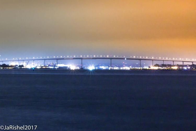 Illuminated city by sea against sky at night