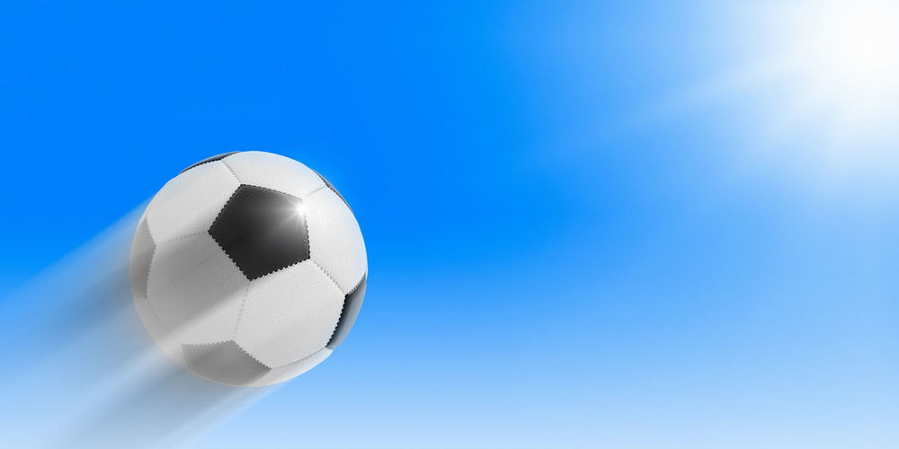 Low angle view of soccer ball against blue sky