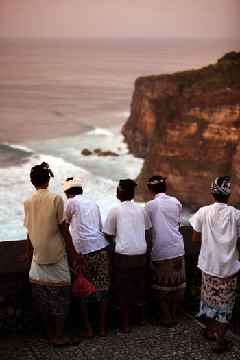 Rear view of boys wearing headdresses standing by retaining wall against sea during sunset