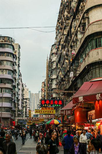 People on city street amidst buildings against sky