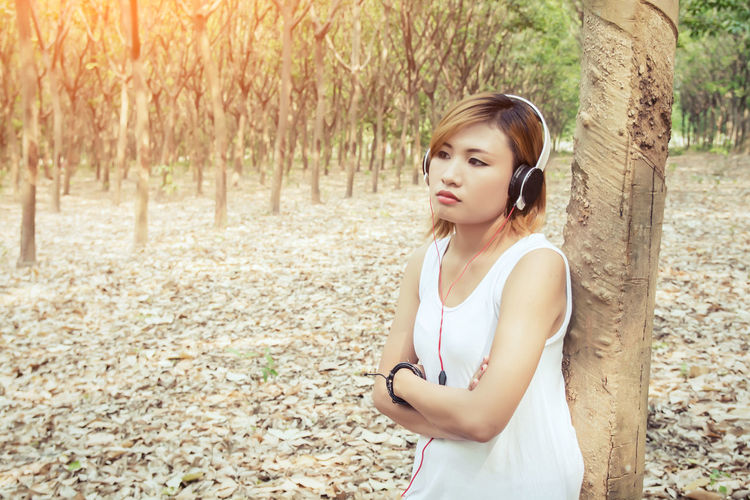 Woman Listening Music Against Trees In Forest