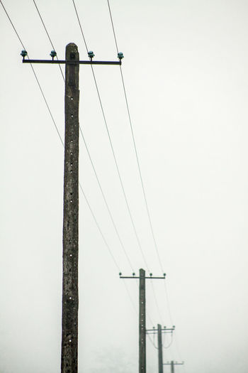 Low Angle View Of Electricity Poles Against Clear Sky