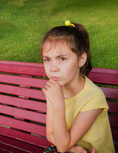 Thoughtful Girl Sitting On Bench