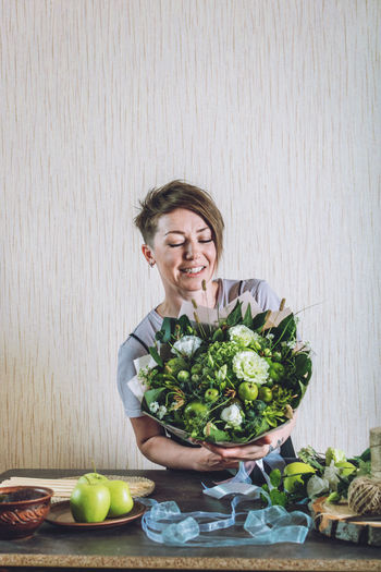 Young woman holding flower arrangement at home