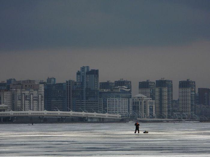 Man walking on frozen sea against buildings in city