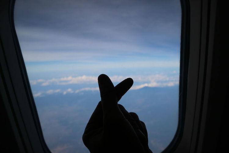 Silhouette hand gesturing by airplane window