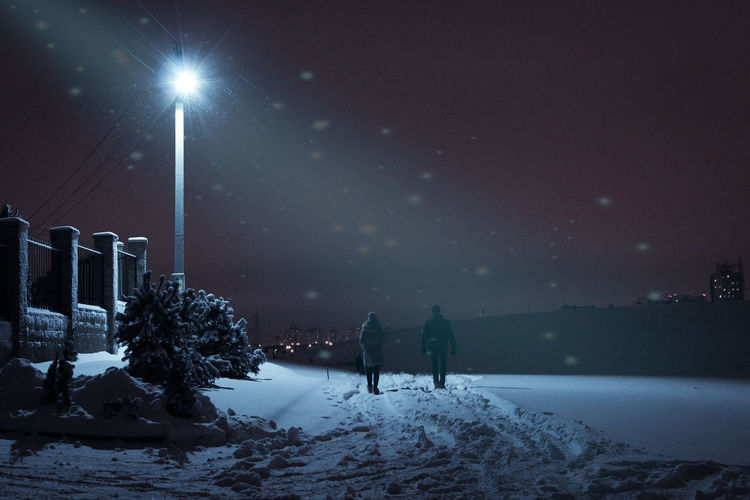 Two people are walking on a snowy road at night by the light of lanterns