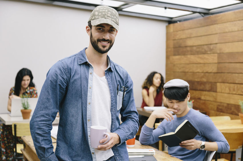Beard Businessman Cap Caucasian Cheerful Coworker Coworking Creative Cup Of Coffee Designer  European  Four People Four Persons Laptop Manager Meeting Modern Espace Multiethnic Group Notebook Office Portrait Professional Young Man