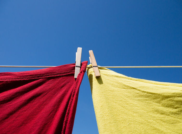 Colour close up of two T-shirts, one red and one yellow, hanging on a washing line with wooden clothes pegs. Shot from below against a clear blue sky Sky Blue Clothesline Textile Red Copy Space Clear Sky Hanging Laundry Drying Day Low Angle View Clothespin No People Sunlight Clothing Outdoors Clean Yellow Washing Colour Image Color Image Clothes Pegs Washing Line