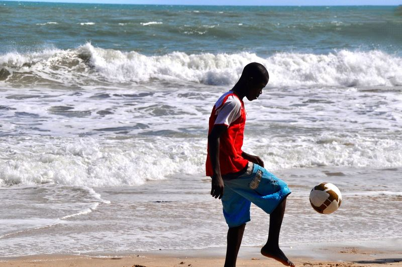 Full length of boy playing soccer on beach