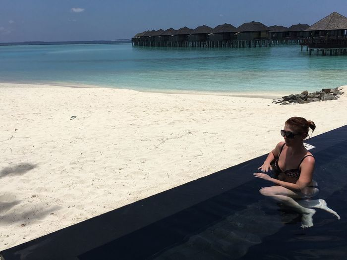 Woman relaxing at infinity pool by beach at manadhoo