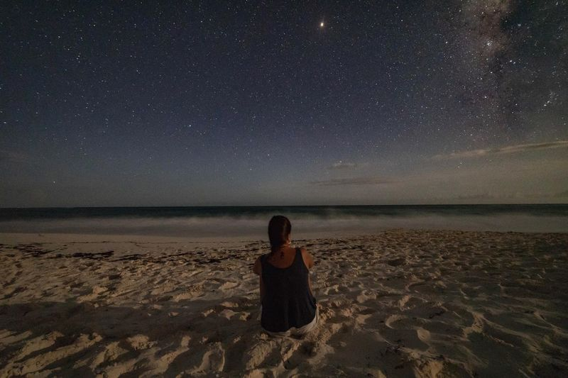 Rear view of man sitting on beach against sky at night