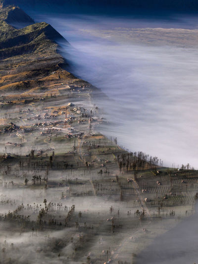 A view of Ngadisari Village in a foggy morning of Bromo Tengger Semeru Park. The Bromo Tengger Semeru National Park covers a massive area of 800 square km in the center of East Java. Exotic INDONESIA Morning Tree Vacations Beauty In Nature Bromo Color Image Day Fog Hill Landscape Leisure Activity Light And Shadow Nature No People Outdoors Scenics Sunrise Tourism Tranquility Travel Destinations Village Fresh On Market 2017