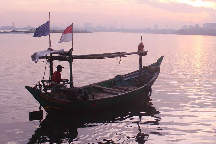 Man sitting on motorboat in lake during sunset