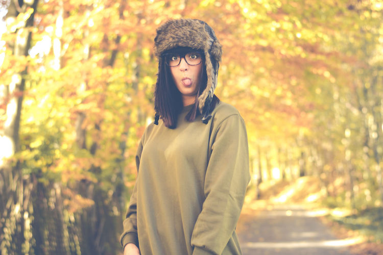 Playful young woman sticking out tongue while standing amidst autumn trees