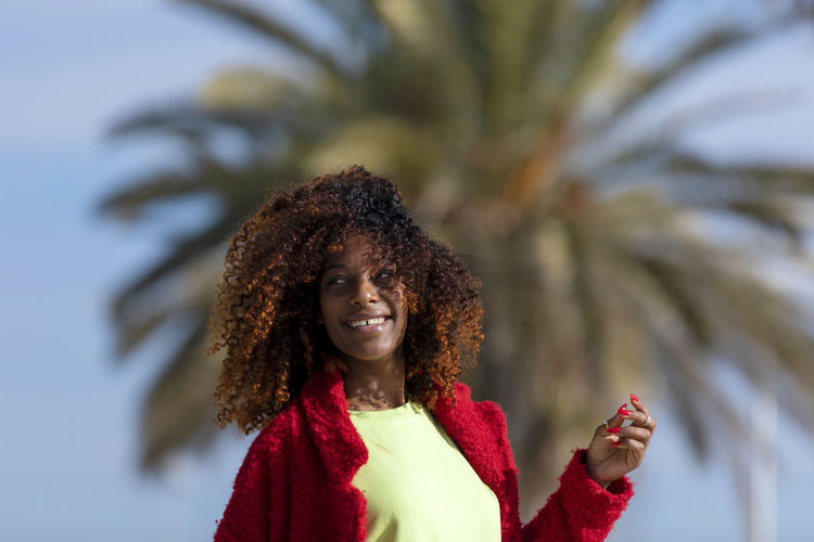 Front view of a young smiling curly afro woman standing outdoors while smiling and looking away in a sunny day One Person Smiling Front View Portrait Happiness Curly Hair Hairstyle Emotion Young Adult Standing Hair Clothing Women Adult Young Women Leisure Activity Cheerful Headshot Outdoors Warm Clothing Beautiful Woman Afro Looking Away