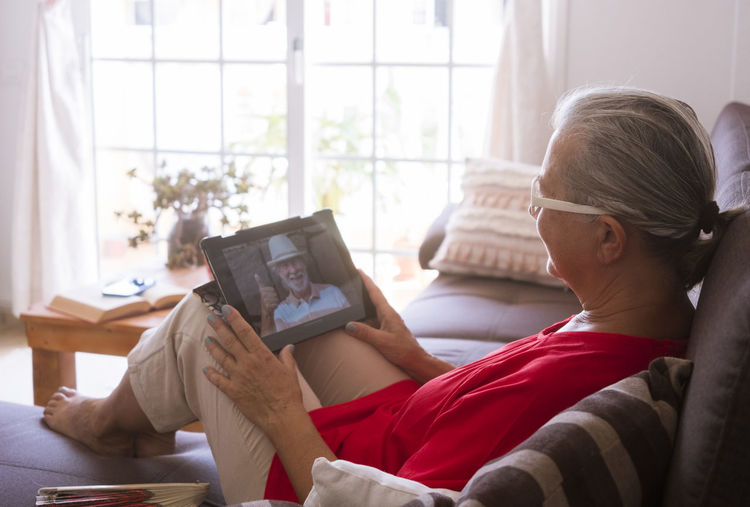 Senior woman holding digital tablet while sitting at home