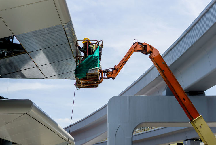 Low angle view of worker working against sky