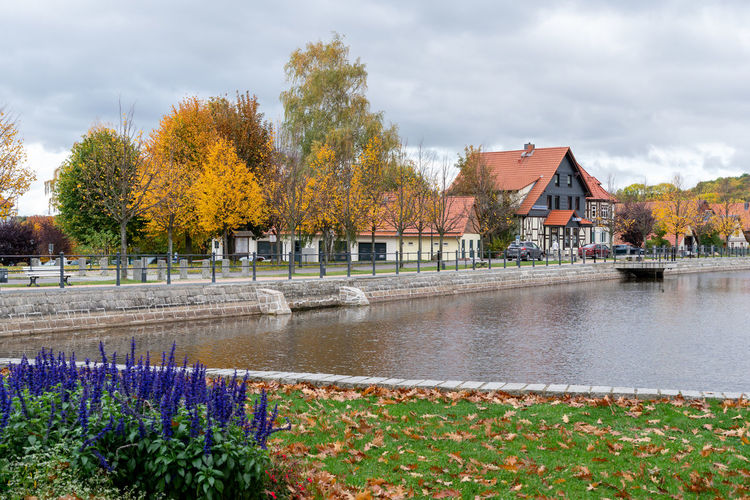 Scenic view of lake by buildings against sky during autumn