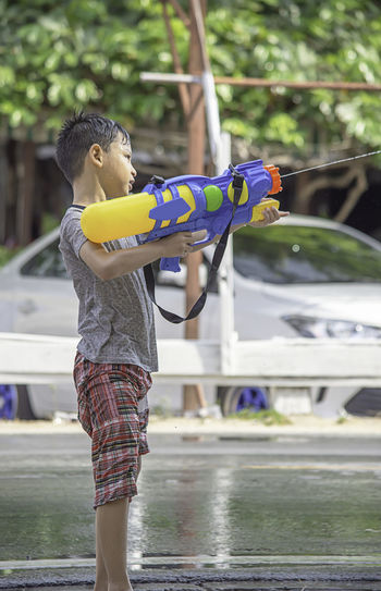Boy playing with squirt gun outdoors