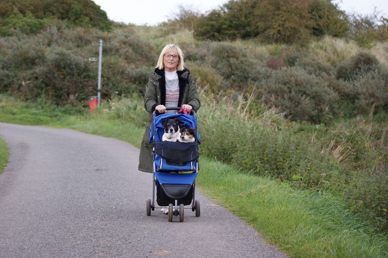 Portrait Of Mature Woman Carrying Dogs In Baby Stroller