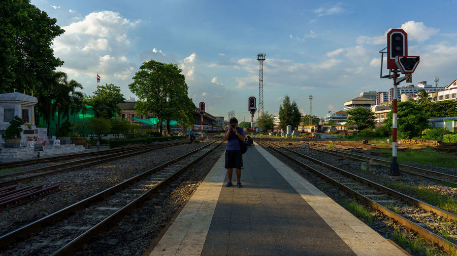 Rear view of woman on railroad station against sky