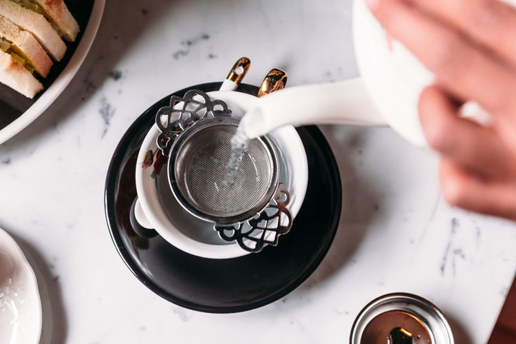 High Angle View Of Hand Pouring Water In Tea Cup