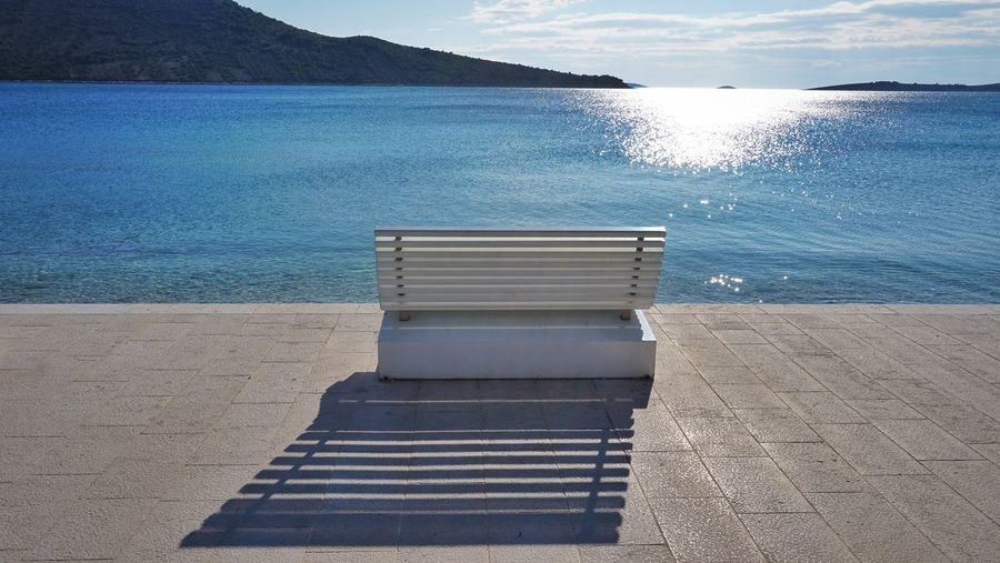 A bench Water Sea Beauty In Nature Nature Tranquility Scenics - Nature Beach Tranquil Scene Land Sunlight Day No People Non-urban Scene Blue Idyllic Cloud - Sky Sky Outdoors