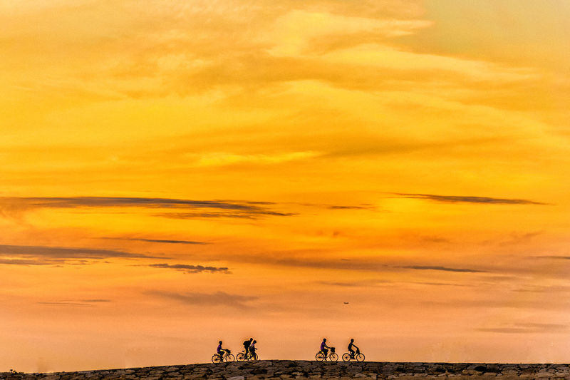 Cyclists riding on field against orange sky