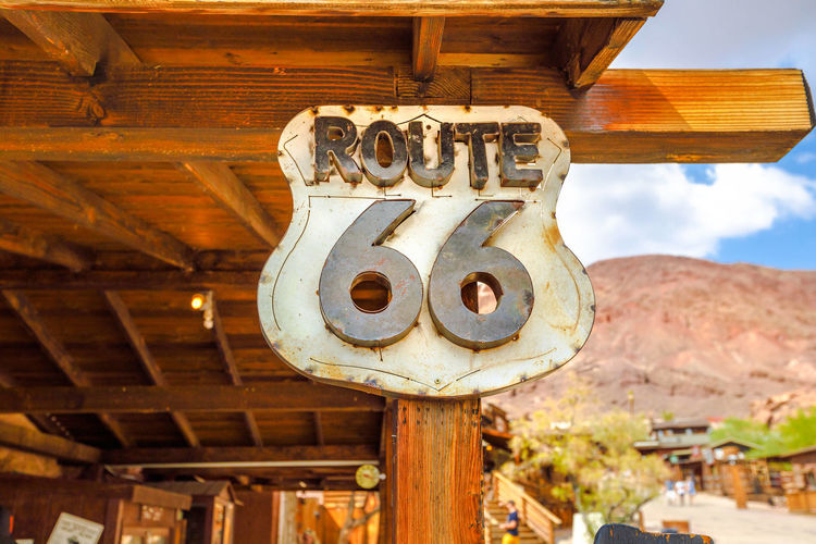 Closeup of Route 66 sign at Calico Ghost Town in blurred background. Mining town in Calico Mountains of Mojave Desert region of Southern California, United States. Calico CalicoGhostTown Calico Ghost Town Ghost Town Town Hall Western Wild West Cowboy Cowgirl Mineral Water Silver Mines Old Vintage Route 66 Old Wild West Mountains Desert California Mojave Desert United States USA America American Building Exterior No People Architecture Built Structure Day Metal Low Angle View Sky Building Outdoors Travel Destinations Mountain Nature History The Past Close-up Wood - Material Focus On Foreground Technology Architectural Column Ceiling Ancient Civilization