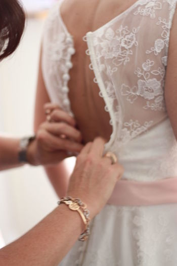 Midsection of bride getting dressed