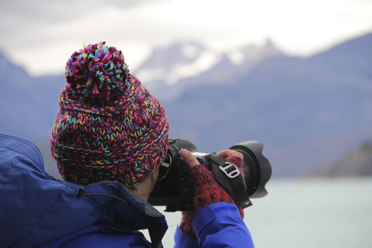 Mountain Winter One Person Warm Clothing Real People Clothing Cold Temperature Mountain Range Snow Leisure Activity Lifestyles Hat Adult Day Nature Knit Hat Scenics - Nature Beauty In Nature Outdoors Rear View Photographer Girl Taking Photos