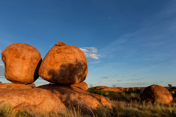 Sunset at the Devils Marbles, Australia. Incredible atmosphere between those unreal rock formations. They look as if they are burning in the sunlight. Atmospheric Mood Beauty In Nature Blue Day Devils Marbles Grass Incredible Nature Karlu Karlu Landscape Marble Nature No People Orange Outdoors Rock - Object Rock Formation Sky Stone Stone Field Sunset