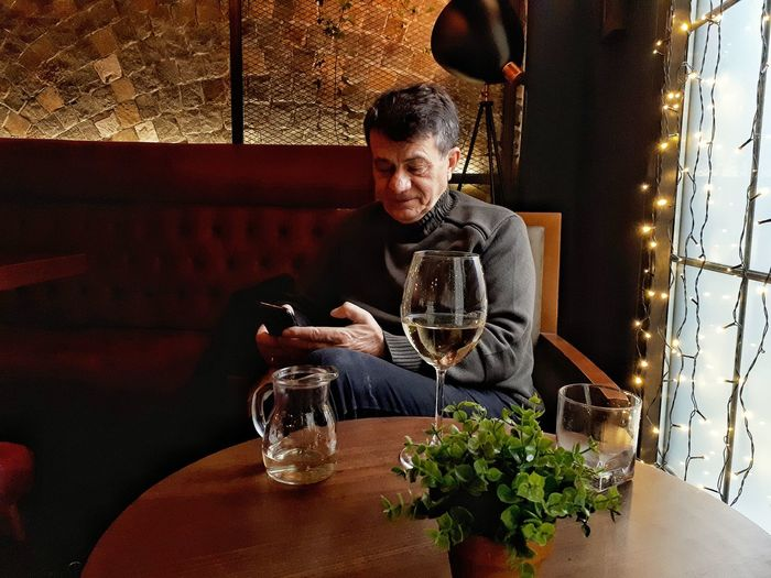 Man using smart phone while sitting on table