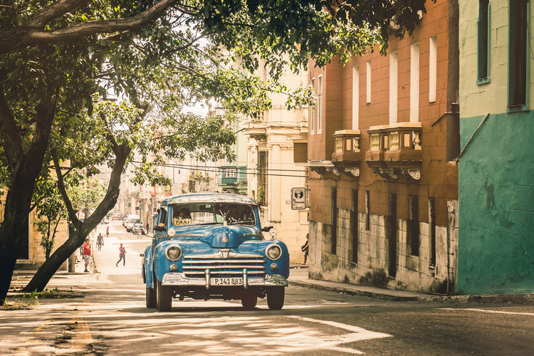 The Traveler - 2018 EyeEm Awards This Is Latin America Architecture Building Exterior Car City City Life Cuba Driving Havana Light And Shadow Old Car Outdoors Road Sommergefühle Street Street Photography Streetphotography Summertime Sunlight Taking Photos Taxi Transportation Tree Vintage Vintage Cars Been There.