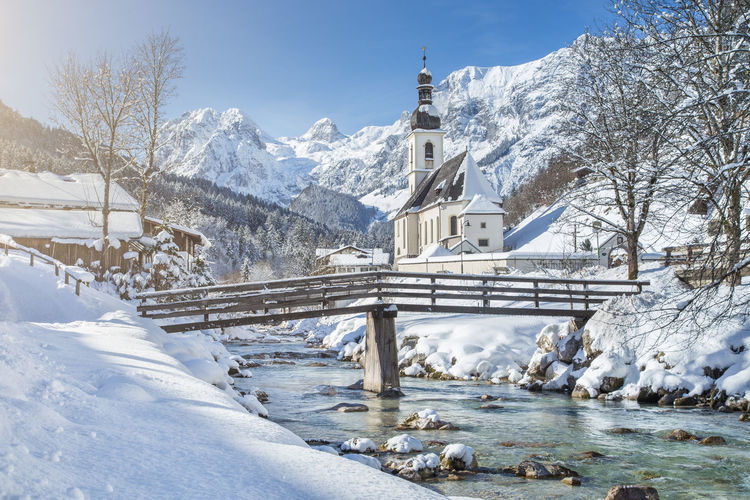 Snow covered church by river against sky
