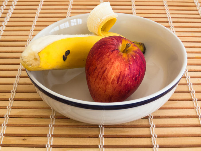 Healthy eating, fresh apple and peeled banana inside bowl on wooden stripes table Apple Banana Bowl Ceramics Dietfood Eating Food Fresh Natural Red Tasty Wooden Yelow Color