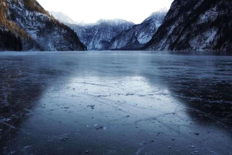 Scenic view of frozen lake against mountains during winter
