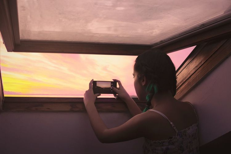 Woman photographing through smart phone at sunset