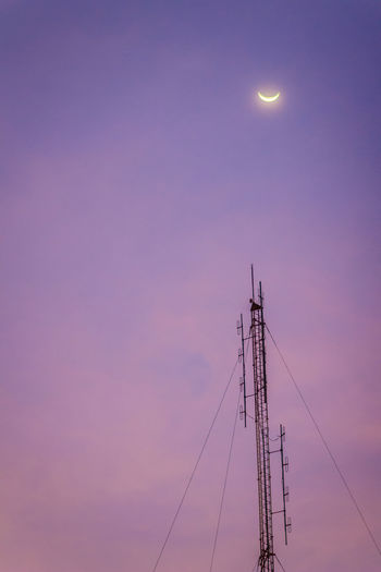 View of the moon on the dusk sky and the folded dipole radio antenna for telecommunications with colorful sky background. Silhouette amateur radio antenna tower in dramatic sky background. Dusk Sky Moon And Stars Moon Rising Telecommunication Tower. Telecommunications Tower Amateur Radio Antenna Tower Architecture Beauty In Nature Built Structure Cable Colorful Sky Beautiful Day Colorful Sky At Night Colorful Sky At Sundown Connection Dusk Dusk Sky Dusk In The City Nightphotography Night Night View Dusk Skyline Electricity  Folded Dipole Fuel And Power Generation Full Moon Low Angle View Moon Moon And Clouds Moon Light Moon On The Blue Sky Moon On The Clear Sky Nature Night No People Outdoors Power Supply Purple Radio Antenna Radio Antennas Scenics - Nature Sky Space Sunset Technology Telecommunication Telecommunication Tower TelecommunicationTower Telecommunications Telecommunications Equipment Tranquility