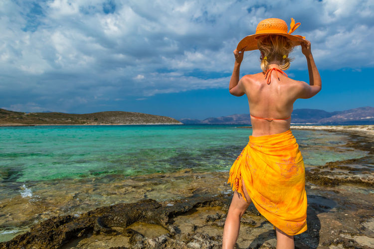 Rear View Of Shirtless Young Woman Standing At Beach