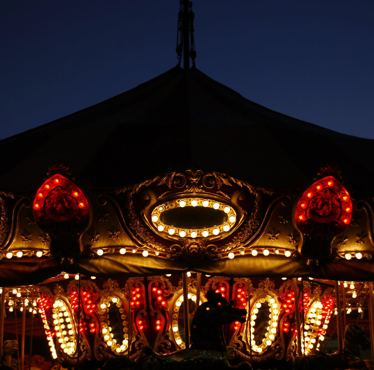 illuminated, sky, lighting equipment, night, amusement park, low angle view, arts culture and entertainment, amusement park ride, carousel, built structure, architecture, no people, building exterior, clear sky, representation, glowing, nature, decoration, red, outdoors, festival, ornate