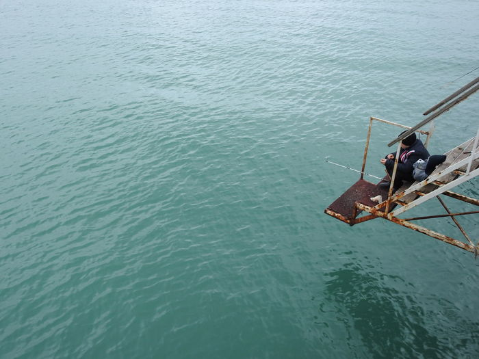 High angle view of man fishing while sitting on staircase by sea
