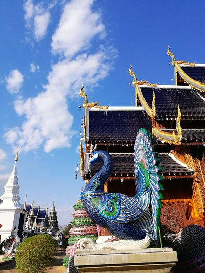 Peacock sculpture in Northern Thailand temple. Sky Architecture No People Building Exterior Outdoors Built Structure Day Beauty In Nature Gold Colored History Sculpture Architecture Tradition Low Angle View Travel Destinations Roof Landscape Clear Sky Blue Spirituality Peacock Tree