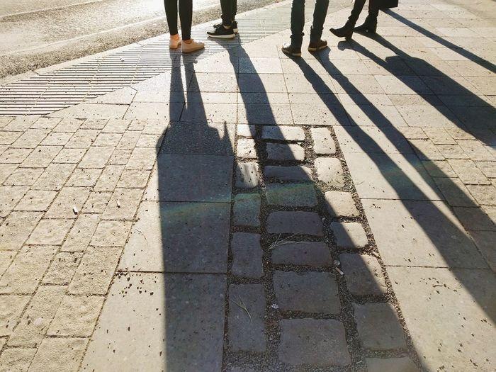 Shadow Of People Walking On Sidewalk